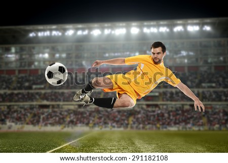 Soccer Player kicking the ball in a football stadium at night - stock photo