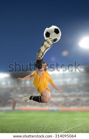 Soccer Player Kicking the ball inside a stadium at night - stock photo
