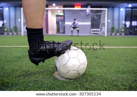 soccer player on penalty kick position with out of focus goalkeeper - stock photo