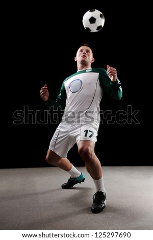 Soccer player over black background - stock photo