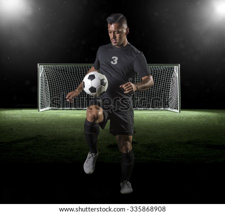 Soccer Player playing soccer on a dark background - stock photo