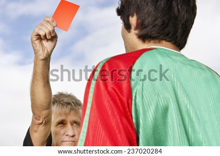 Soccer Player Receiving Red Card - stock photo