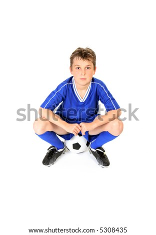 Soccer player resting on soccer ball.
