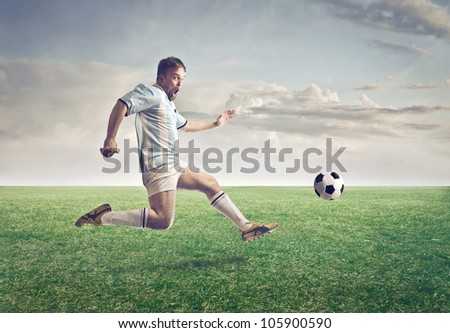 Soccer player running after a ball on a meadow