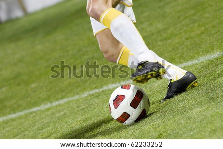 Soccer player running after the ball - stock photo