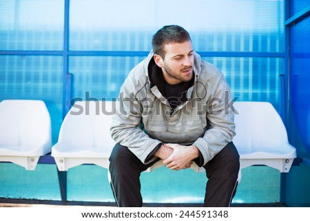 Soccer player sitting on the bench. Prepering for match. - stock photo