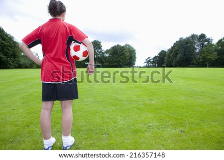 Soccer player with ball looking down field