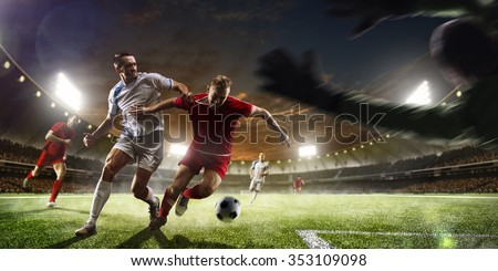 Soccer players in action on the sunset stadium background panorama - stock photo