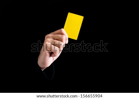 Soccer referee giving yellow card on black background. - stock photo