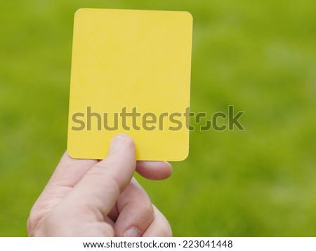 Soccer referee hand with yellow card - stock photo