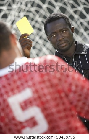 Soccer referee holding out yellow card, portrait