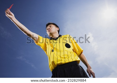Soccer Referee Holding Penalty Card - stock photo