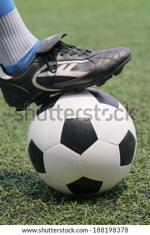 Soccer shoes and football in artificial grass - stock photo