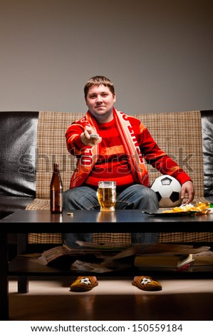 soccer supporter is sitting on sofa in red jersey