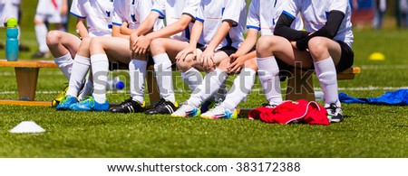 Soccer youth team; Reserve Players on a bench; Boys With Football Coach - stock photo