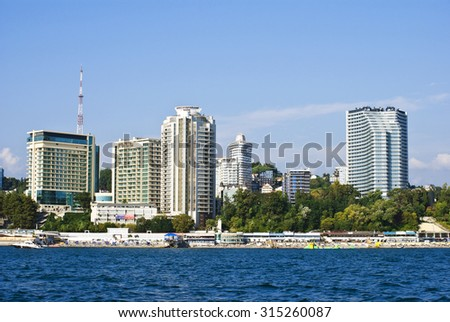 SOCHI, RUSSIA, AUGUST 28, 2015  Tourists relax on the background buildings in Sochi, view from the sea