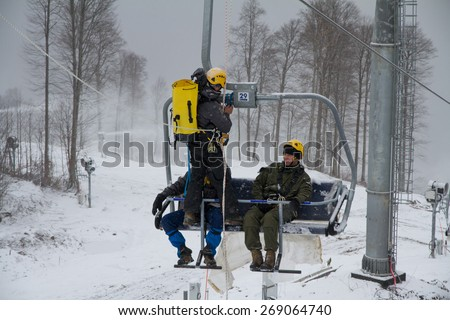 "SOCHI, RUSSIA - DECEMBER 12, 2013: Rescuers rehearse rescue on the ski lift. Mountain resort ""Rosa Khutor"". - stock photo"