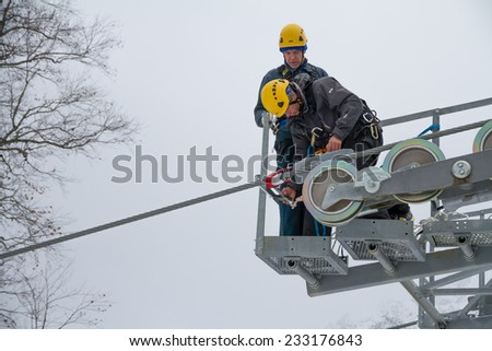 "SOCHI, RUSSIA - DECEMBER 12, 2013: Workers repairing the ski lift in mountain resort ""Rosa Khutor""."