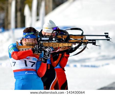 "SOCHI, RUSSIA - FEBRUARY 9: IBU Regional Cup in Sochi on February 9, 2013. The combined ski-biathlon complex ""Laura"". Male prosecution race, Stanislav Bazeev on a firnig line. - stock photo"