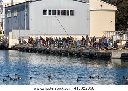 Sochi, Russia - February 9, 2016: Many anglers are fishing from the pier in the sea port of Sochi - stock photo