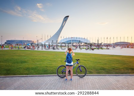 SOCHI, RUSSIA - JUL 27, 2014: Tourists walk in the Olympic park with a bowl of the Olympic flame and the stadium Fischt - stock photo
