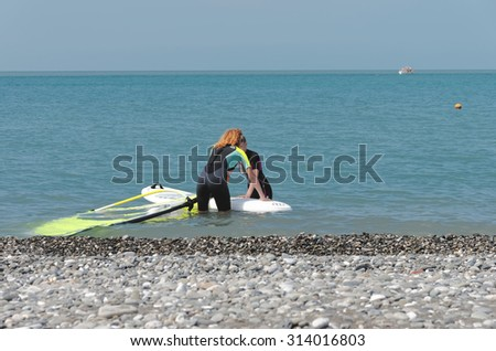 SOCHI, RUSSIA - JUNE 10, 2015: Windsurfers in Sochi, young woman to take serfing training of from a coach.