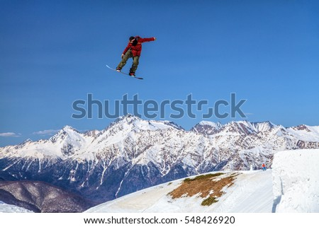 Sochi, Russia - March 25, 2014: Quiksilver Camp is a winter sports and entertainment activity for skiers and snowboarders. Snowboarder flies from a jump in the air on blue sky and mountain background