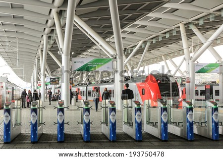 "SOCHI,RUSSIA - MARCH 6, 2014: Turnstiles to the railway platform of modern and futuristic design under big beautiful roof with high-speed electric train ""Lastochka"" at the Olympic Park Railway Station - stock photo"