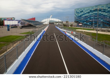 SOCHI, RUSSIA - SEPTEMBER 28, 2014: Line of championship Formula 1 in Sochi in Olmpijsky park against Ice palace and Olympic torch. Preparation of competition to be held on 12 October 2014 - stock photo