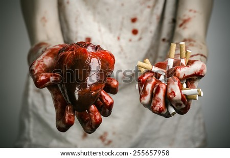 Social advertising and tobacco control: bloody hand holding a cigarette smoker and bloody human heart - stock photo