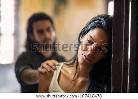 Social issues, domestic violence with young husband trying to reconcile with abused wife - stock photo