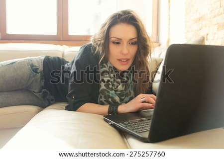 Social media addict. Beautiful caucasian woman relaxing on the couch, chatting with her friends online. - stock photo