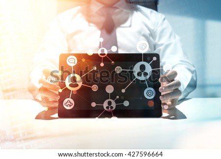 Social network concept with businessman showing tablet with abstract connect icons - stock photo