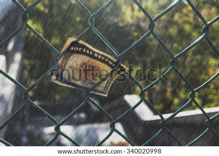 social security card stuck on fence in rain - stock photo