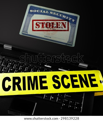 Social Security card with Stolen stamp on a laptop with crime scene tape -- Identity Theft concept - stock photo