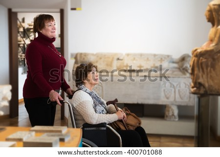 Social worker and female pensioner in wheelchair at museum - stock photo