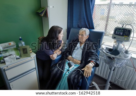 Social worker visit sick old male patient in hospital. - stock photo