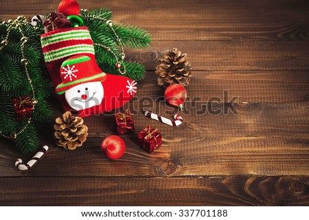 sock with toys and gifts on wooden background with Christmas tree
