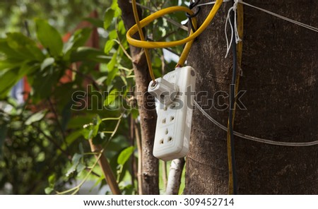 Socket hanging on a tree with yellow wire. Concept of dangerous electric using. - stock photo
