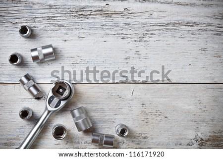 Socket wrench on painted wood background - stock photo