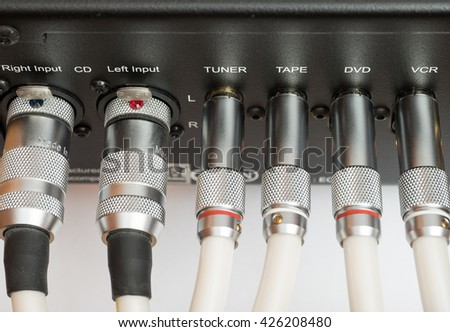 Sockets and plugs of the inputs and outputs on an black metal panel. It is part of the rear panel of the amplifier. - stock photo