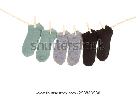 socks hanging on a rope clothesline isolated on white - stock photo