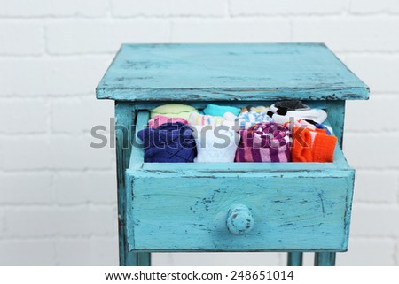 Socks in color drawer on white brick wall background - stock photo