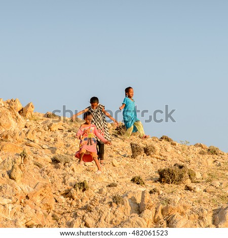 SOCOTRA, YEMEN - JAN 12, 2014: Unidentified Yemeni little children run down a hill to the beach of the Island of Socotra. Children in Socotra live in poverty and grow without education