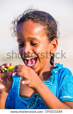 SOCOTRA, YEMEN - JAN 12, 2014: Unidentified Yemeni little girl eats a candy  on  the beach of the Island of Socotra. Children in Socotra live in poverty and grow without education