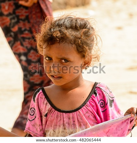 SOCOTRA, YEMEN - JAN 12, 2014: Unidentified Yemeni little girl on the beach of the Island of Socotra. Children in Socotra live in poverty and grow without education