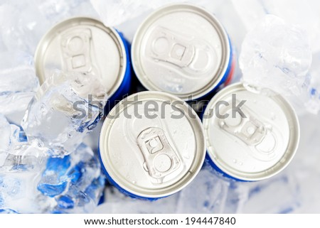 Soda cans in ice with condensation - drink can - stock photo