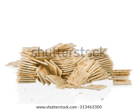 Soda crackers stacks fallen mess isolated on white background - stock photo