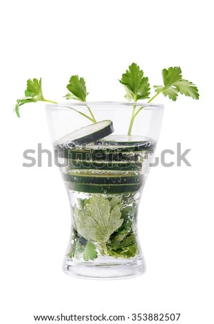 Soda water with parsley and cucumber on white background