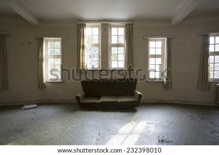 sofa chair in empty creepy room by windows - stock photo